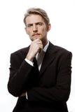 Jeune homme d'affaires réussi pensant avec la main sur le menton au-dessus du fond blanc Photos stock