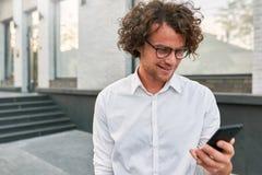 Jeune homme d'affaires réussi se tenant dehors et à l'aide du smartphone et de la radio libre Homme caucasien avec le port de che image stock