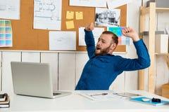 Jeune homme d'affaires réussi somnolent s'asseyant sur le lieu de travail avec l'ordinateur portable Fond de bureau Photos stock