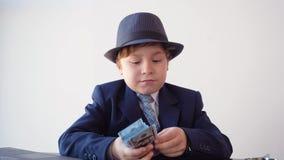 Jeune homme d'affaires racontant le billet de banque du dollar et regardant par la loupe Homme d'affaires scrupuleux vérifiant l' clips vidéos