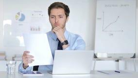 Jeune homme d'affaires Reading Documents au travail banque de vidéos