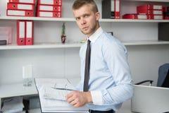 Jeune homme d'affaires Reading Some Papers dans le bureau image stock