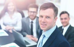 Jeune homme d'affaires regardant l'appareil-photo sur le fond de son équipe Image libre de droits