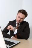 Jeune homme d'affaires regardant la montre-bracelet Photographie stock libre de droits