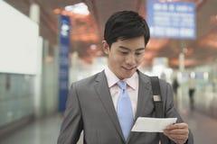 Jeune homme d'affaires regardant le billet l'aéroport, Pékin, Chine Photo libre de droits