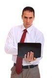 Jeune homme d'affaires restant avec l'ordinateur portatif Image stock