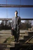 Jeune homme d'affaires restant sur des escaliers images stock