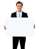 Jeune homme d'affaires retenant le panneau-réclame blanc blanc images libres de droits
