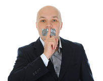 Jeune homme d'affaires retenant un doigt sur sa bouche. Photographie stock