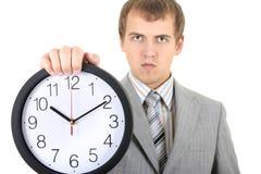 Jeune homme d'affaires retenant une horloge Photo libre de droits