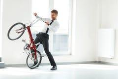 Jeune homme d'affaires Rides sur son vélo au bureau Gens d'affaires Photo libre de droits