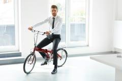 Jeune homme d'affaires Rides sur son vélo au bureau Gens d'affaires Photo stock