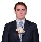Jeune homme d'affaires sérieux avec l'ours de nounours dans le procès Photographie stock libre de droits