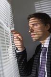 Jeune homme d'affaires sérieux jetant un coup d'oeil par des abat-jour dans le bureau Image libre de droits