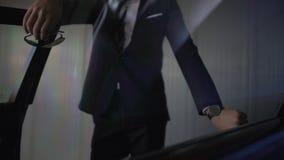Jeune homme d'affaires sûr se penchant sur sa voiture de luxe, flirtant avec quelqu'un banque de vidéos