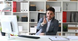 Jeune homme d'affaires s'asseyant à la table dans le bureau blanc, souriant et montrant le geste de main avec approbation banque de vidéos