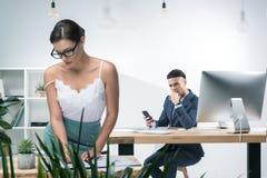 Jeune homme d'affaires s'asseyant au bureau et regardant la femme d'affaires séduisante travaillant dans le bureau Image stock