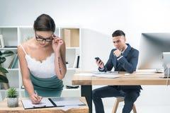 Jeune homme d'affaires s'asseyant au bureau et regardant la femme d'affaires séduisante travaillant dans le bureau Image libre de droits