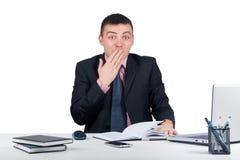Jeune homme d'affaires s'asseyant au bureau et semblant choqué Photographie stock libre de droits