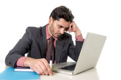 Jeune homme d'affaires s'asseyant au bureau travaillant à désespéré d'ordinateur portable d'ordinateur inquiété dans des contrain Image libre de droits