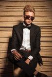 Jeune homme d'affaires s'asseyant avec ses jambes croisées Photos stock