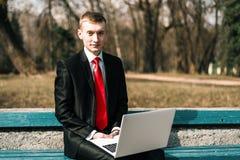 Jeune homme d'affaires s'asseyant avec un ordinateur portable sur un banc de parc type dans un costume avec un lien rouge ind?pen photos stock