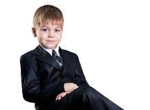 Jeune homme d'affaires s'asseyant dans le procès noir d'isolement photo stock