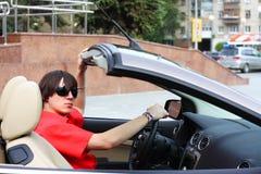 Jeune homme d'affaires s'asseyant dans une voiture Photos stock