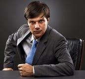 Jeune homme d'affaires s'asseyant derrière le bureau images stock