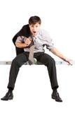 Jeune homme d'affaires s'asseyant sur l'échelle. D'isolement Image libre de droits