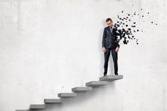 Jeune homme d'affaires se brisant dans de petits morceaux sur les escaliers sur le fond blanc photo libre de droits