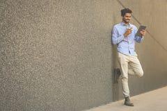 Jeune homme d'affaires se penchant contre le mur avec le comprimé numérique Homme photos libres de droits