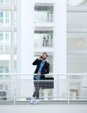 Jeune homme d'affaires se tenant avec le téléphone portable Photo stock