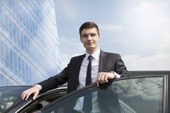 Jeune homme d'affaires se tenant près de sa voiture Photo stock