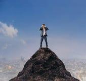 Jeune homme d'affaires se tenant sur la montagne et remarquant par la poubelle Photos libres de droits