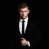 Jeune homme d'affaires se tenant sur le fond noir Homme bel dans le costume et le lien Photographie stock
