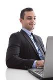 Jeune homme d'affaires semblant satisfait avec l'ordinateur portable d'isolement sur le whi photo libre de droits