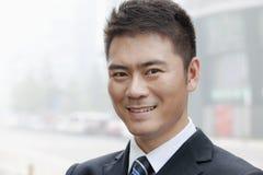 Jeune homme d'affaires Smiling et regard dans l'appareil-photo, portrait Photographie stock libre de droits
