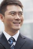 Jeune homme d'affaires Smiling et regard loin, portrait Photographie stock