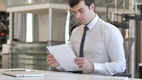 Jeune homme d'affaires songeur Reading Contract dans le bureau clips vidéos