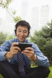 Jeune homme d'affaires souriant et écoutant la musique sur son joueur MP4 en parc Photo libre de droits