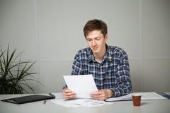 Jeune homme d'affaires souriant tout en lisant un rapport dans le lieu de travail Photographie stock