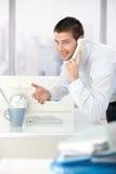 Jeune homme d'affaires sur le sourire de téléphone Photographie stock libre de droits