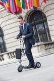 Jeune homme d'affaires sur un scooter de pédale Photographie stock