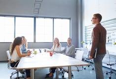 Jeune homme d'affaires sur une réunion avec des employés de bureau sur un fond de pièce Concept de technologie Copiez l'espace Image libre de droits