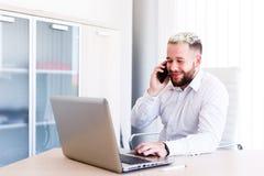 Jeune homme d'affaires Talking On Phone tandis que travaux sur l'ordinateur portable photographie stock