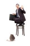 Jeune homme d'affaires tenant la serviette se tenant sur la chaise terrifiée photo libre de droits