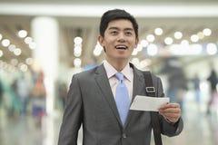 Jeune homme d'affaires tenant le billet à l'aéroport, Pékin, Chine Photos stock