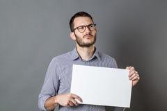 Jeune homme d'affaires tenant une bannière vide avec l'imagination Photographie stock libre de droits