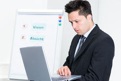 Jeune homme d'affaires travaillant à l'ordinateur portatif Photos libres de droits